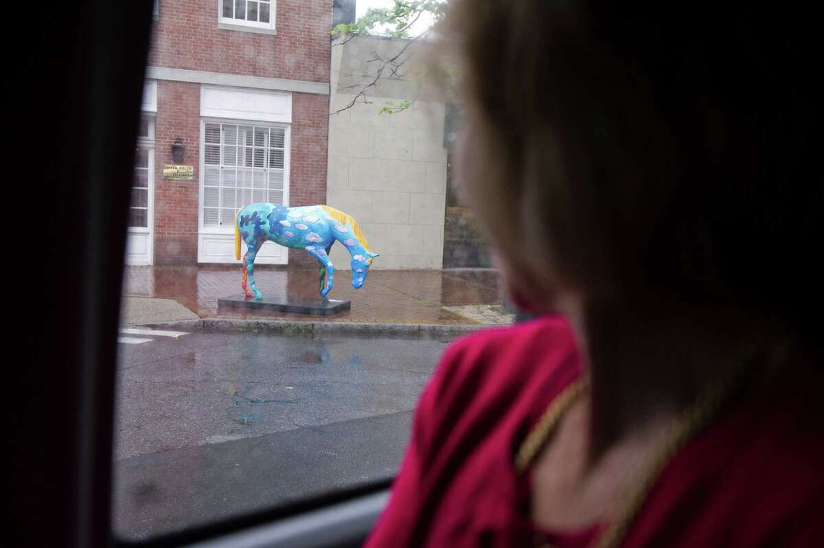 Ilene Locker takes in the horse sculptures stationed throughout the Downtown area during a tour hosted by Stamford's Downtown Special Services District during the opening night reception for Horsin' Around in Stamford, Conn., June 12, 2012.