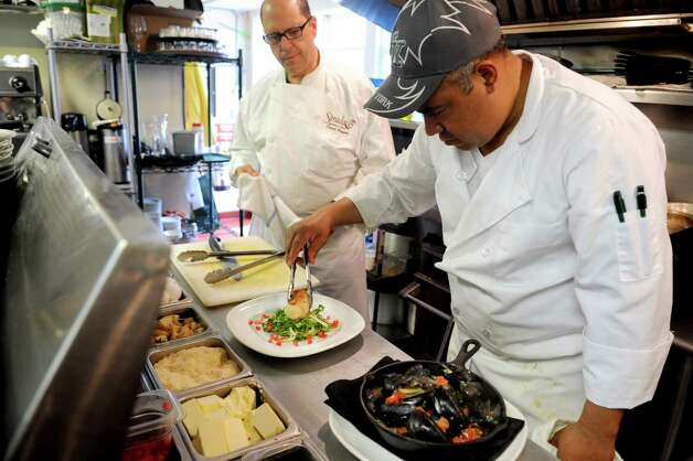 Line cook Bartolo Campos plates a seafood sausage as chef/owner David Raymer looks on at Boulevard 18 in New Canaan on Tuesday, May 22, 2012. Photo: Lindsay Niegelberg / Stamford Advocate