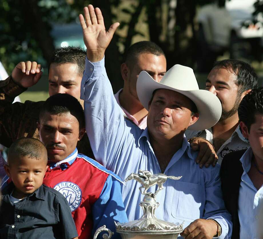 In this photo taken Sept. 6, 2010, owner Jose Trevino Morales, center, acknowledges the crowd as he stood with the trophy after Mr. Piloto won the All American Futurity horse race at Ruidoso Downs, N.M. Federal agents raided a sprawling ranch in Oklahoma and the prominent quarter horse track in New Mexico on Tuesday, June 12, 2012, alleging the brother of a high-ranking official in a Mexican drug cartel used a horse-breeding operation to launder money. Seven of the 14 people indicted were arrested, including Jose Trevino Morales. (AP Photo/The El Paso Times, Rudy Gutierrez) EL DIARIO OUT; JUAREZ MEXICO OUT; Photo: Rudy Gutierrez, AP / El Paso Times