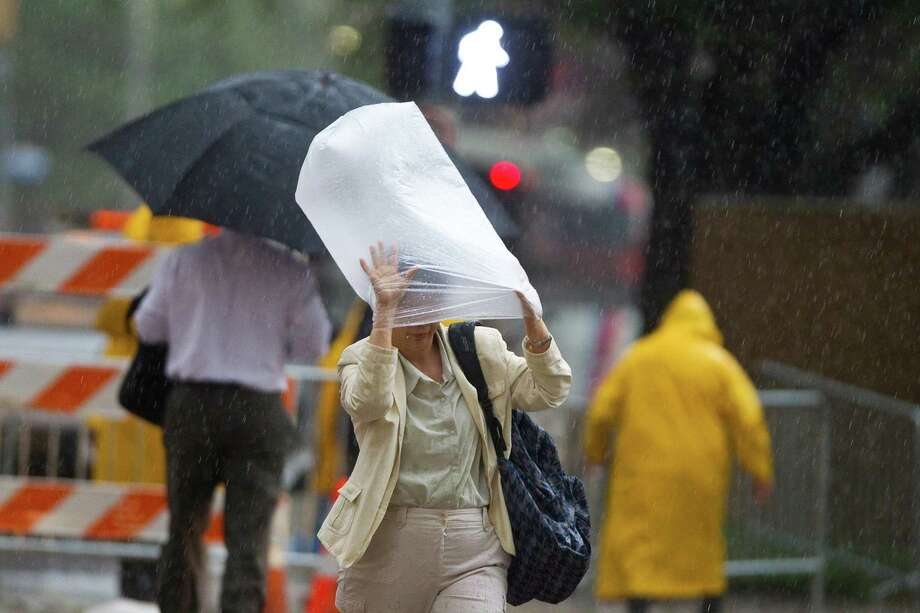 A woman uses a plastic back to shield herself from the rain as she crosses Rusk Street during a down pour, Tuesday, June 12, 2012, in Houston. Photo: Nick De La Torre, Houston Chronicle / © 2012  Houston Chronicle