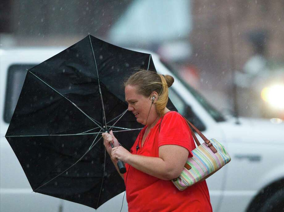 Melinda Forthman's umbrella turns up in the wind as she crosses Capitol Street to wait for the bus at her stop, Tuesday, June 12, 2012, in Houston. Photo: Nick De La Torre, Houston Chronicle / © 2012  Houston Chronicle