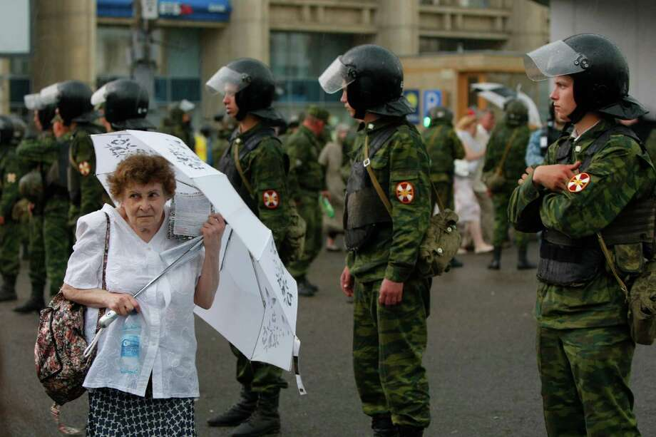 An elderly woman holds a white umbrella as a symbol of protest, as she walks past a line of police officers after a massive opposition rally in central Moscow, Russia, Tuesday, June 12, 2012. Tens of thousands of Russians flooded Moscow's tree-lined boulevards Tuesday in the first massive protest against President Vladimir Putin's rule since his inauguration, as investigators sought to raise the heat on the opposition by summoning some of its leaders for questioning just an hour before the march. Photo: Alexander Zemlianichenko, Associated Press / AP