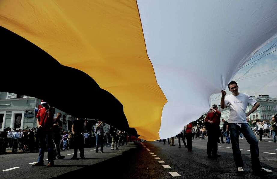 Nationalists carry a huge black-yellow-white flag of the Russian Empire as they take part in anti-Pu