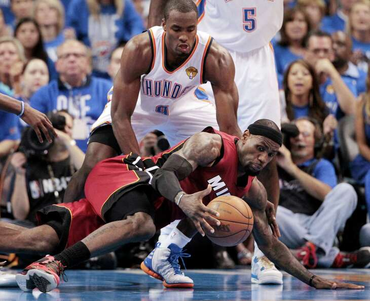 Miami Heat small forward LeBron James  grabs a loose abll as Oklahoma City Thunder power forward Ser