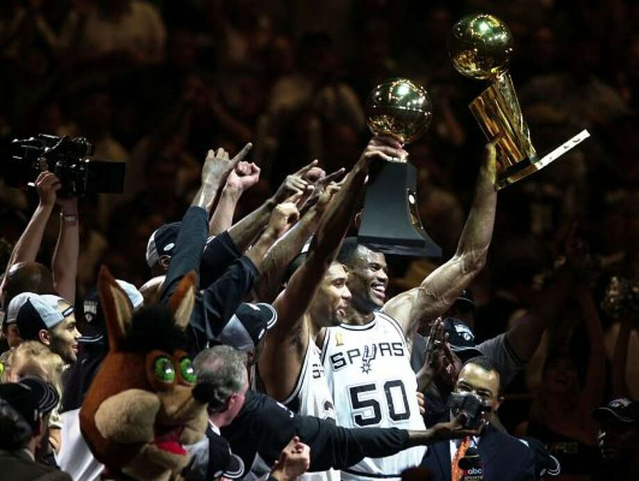 Tim Duncan and David Robinson hold up the hardware as they celebrate Sunday, June 15, 2003 at the SBC Center. The Spurs beat the Nets 88-77 in game 6 to win the NBA Championship.  (BAHRAM MARK SOBHANI / SAN ANTONIO EXPRESS-NEWS)
