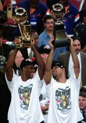 Spurs' David Robinson (left) and Finals MVP Tim Duncan rise their trophies at the end of Game Five of the NBA Finals Friday June 25, 1999 in Madison Square Garden in New York City. (Kin Man HUi / Express-News)