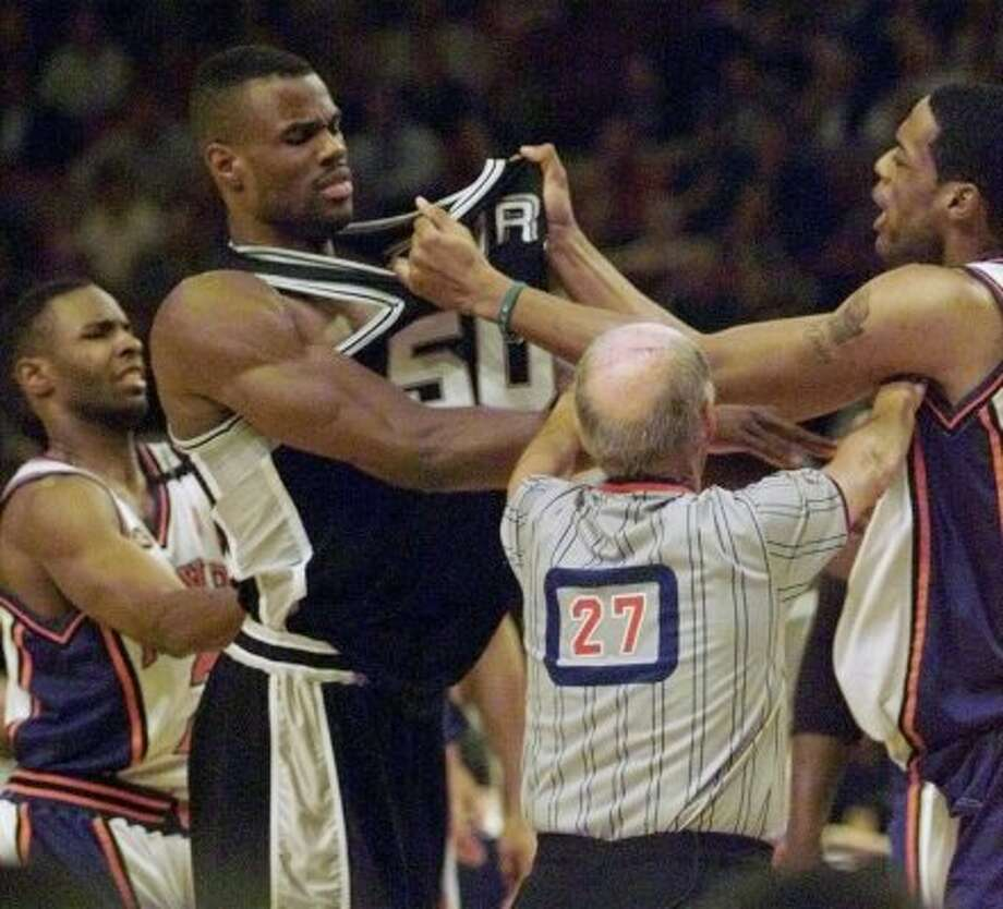 Referee Dick Bavetta seperates marcus Camby and David Robinson in  the third quarter of  game three of the NBA finals  Monday June 21, 1999 at Madison Square Garden in New York City.  (DELCIA LOPEZ / Express-News)