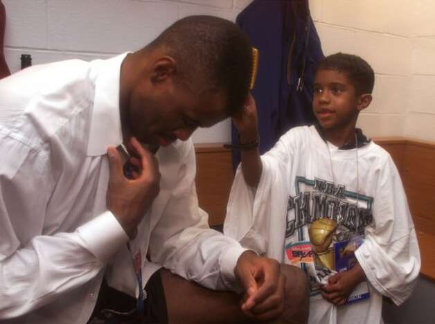 David Maurice Robinson helps his father get dressed after Game Five of the NBA Finals Friday June 25, 1999 in Madison Square Garden in New York City.  (JERRY LARA / Express-News)