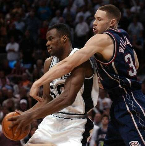 David Robinson pulls down a rebound over New Jersey's Aaron Williams during fourth quarter action of game six of the NBA Finals at the SBC Center in San Antonio on Sunday, June 15, 2003.  (Kin Man Hui / SAN ANTONIO EXPRESS-NEWS)