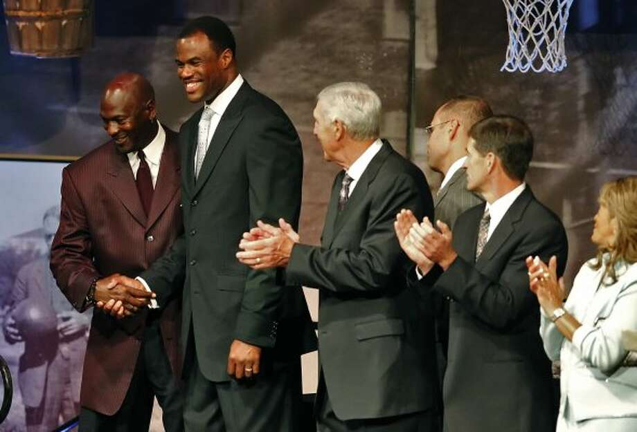 Retired Spur and 2009 Hall of Fame inductee David Robinson (second from left) shakes hands with fellow inductee Michael Jordan as the rest of this year's class including Jerry Sloan, John Stockton and C. Vivian Stringer applaud at the reunion dinner held at the Naismith Memorial Basketball Hall of Fame in Springfield, Mass. on Thursday, Sept. 10, 2009. The group will be officially honored on Friday.  (KIN MAN HUI / San Antonio Express-News)