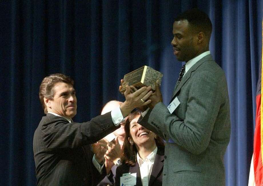 Former San Antonio Spurs player David Robinson, who is the main benefactor of the Carver Academy, right, receives the Texan of the Year award from Gov. Rick Perry in New Braunfels on Friday, March 26, 2004.  (BILLY CALZADA / SAN ANTONIO EXPRESS-NEWS)