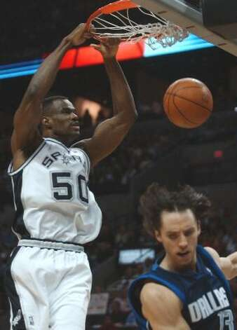 Spurs' David Robinson follows through on a slam dunk against Dallas Mavericks'  Steve Nash in the first quarter at game 5 of the Western Conference Finals at the  SBC Center in San Antonio on Tuesday, May 27, 2003.  (Kin Man Hui / SAN ANTONIO EXPRESS-NEWS)