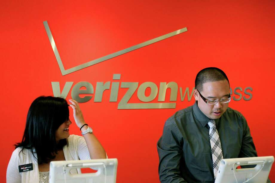 Two Verizon workers take orders at a Verizon store in Mountain View, Calif., Tuesday, June 12, 2012. Verizon Wireless, the nation's largest cellphone company, announced Tuesday  that is dropping nearly all of its phone plans in favor of pricing schemes that encourage consumers to connect their non-phone devices, like tablets and PCs, to Verizon's network. (AP Photo/Paul Sakuma) Photo: Paul Sakuma / AP