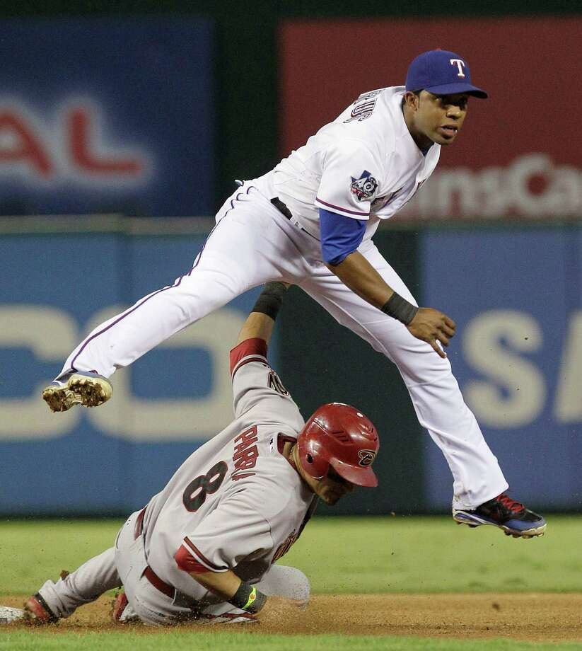 Texas Rangers shortstop Elvis Andrus jumps over a forced-out Arizona Diamondbacks' Gerardo Parra and watches his throw to first during the seventh inning of a baseball game, Tuesday, June 12, 2012, in Arlington, Texas. Willie Bloomquist was safe at first. Photo: AP