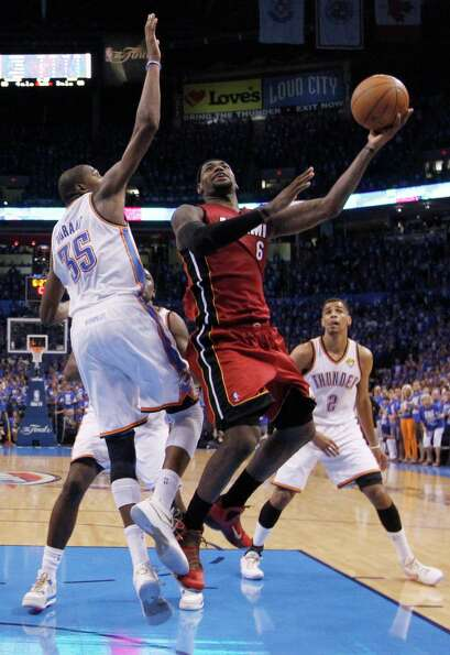 Miami Heat small forward LeBron James shoots against Oklahoma City Thunder small forward Kevin Duran