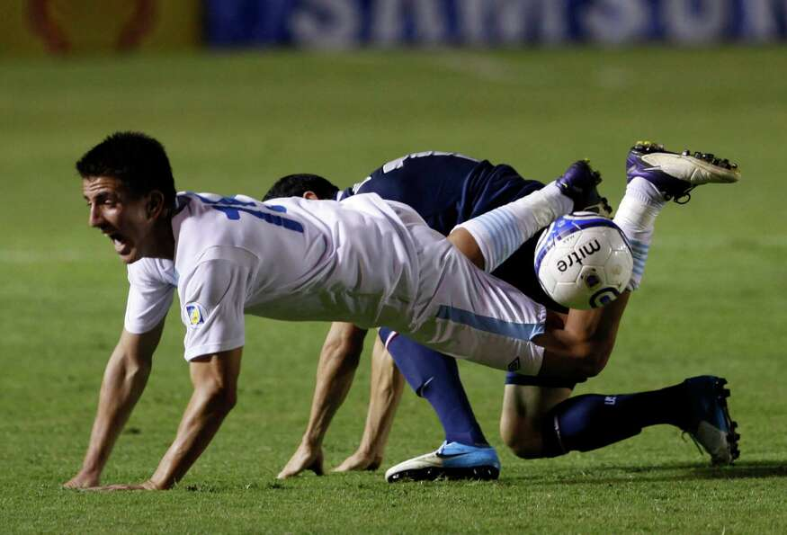 Guatemala's Manuel Leon, front, and United States' Landon Donovan fight for the ball.