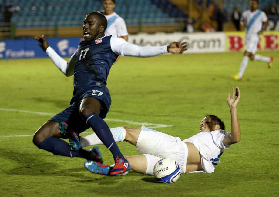 Guatemala's Luis Rodriguez, right, tackles United States' Josmer Altidore. Photo: Rodrigo Abd, Associated Press / AP