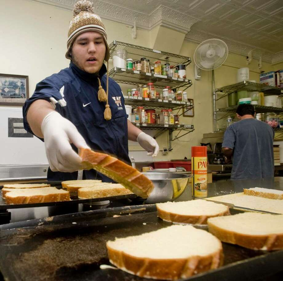 WestConn football sophomore Alan Quintero of Norwalk prepares French toast at the Dorothy Day Hospitality house. WestConn kids serve breakfast four days a week in a program run by Catholic Charities. Wednesday, Nov. 18, 2009 Photo: Scott Mullin / The News-Times