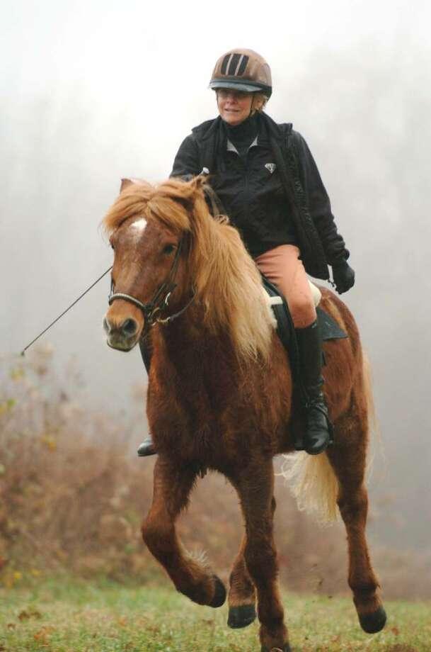 Patrice Passaro of Bethel, rides her horse Brau at Huntington State Park, Bethel,  Wednesday, Nov. 25, 2009. Photo: Chris Ware / The News-Times