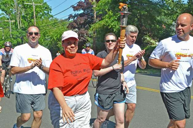 Jassinia Mysogland carries the torch alongside Darien and New Canaan police officers as she runs through Darien, Connecticut during the Special Olympics Law Enforcement Torch Run last Friday morning, June 8, 2012. Photo: Jeanna Petersen Shepard