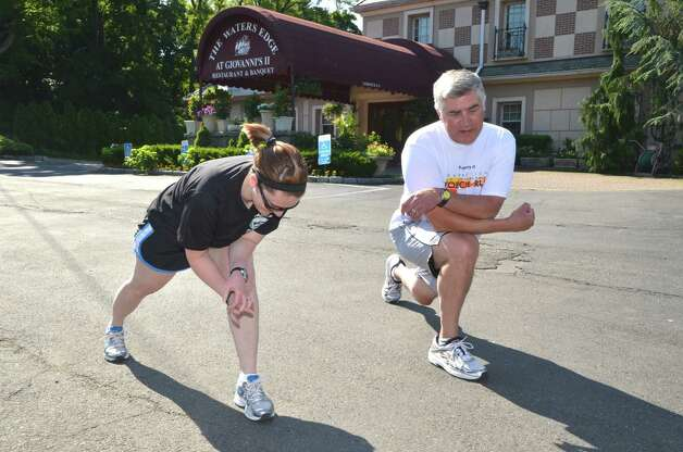 Darien officer Kate Gelineau and Chief of Police Duane Lovello stretch as they wait for the runners to cross the Stamford-Darien line during the Special Olympics Law Enforcement Torch Run last Friday, June 8, 2012.  Darien, Conn. Photo: Jeanna Petersen Shepard