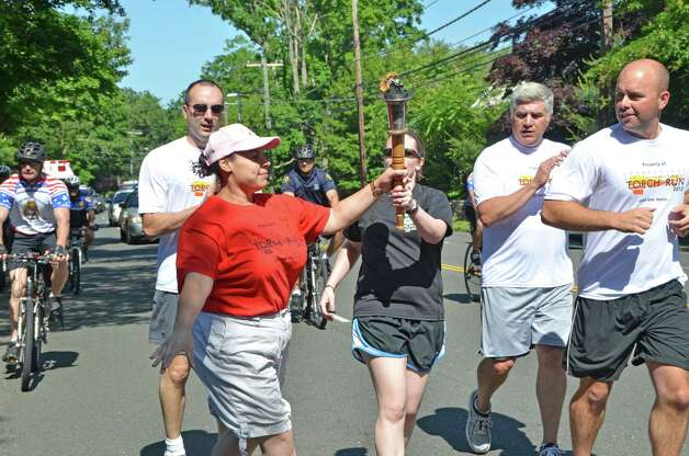 Darien Police Officer Kate Gelineau passes the torch to Special Olympian Jassinia Mysogland during the Special Olympics Law Enforcement Torch Run, alongside New Canaan Officer Brian Mitchell, Darien Police Chief Duane Lovello and New Canaan Officer Ron Bentley.  June 8, 2012, Darien, Conn. Photo: Jeanna Petersen Shepard