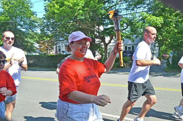 A happy Jassinia Mysogland runs through Darien carrying the Special Olympics torch!  June 8, 2012, Darien, Conn. Photo: Jeanna Petersen Shepard