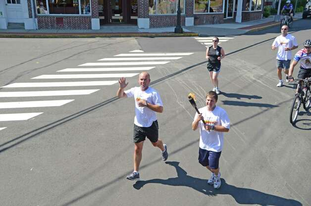 New Canaan Police Officers Ron Bentley and Marc deFelice run through the center of Darien, Connecticut during the Special Olympics Law Enforcement Torch Run last Friday morning, June 8, 2012. Photo: Jeanna Petersen Shepard