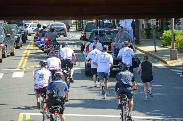 New Canaan police officers run through the center of Darien with other law enforcement officers/cyclists and emergency vehicles pulling up the rear during the Special Olympics Law Enforcement Torch Run last Friday morning, June 8, 2012.  Darien, Conn. Photo: Jeanna Petersen Shepard