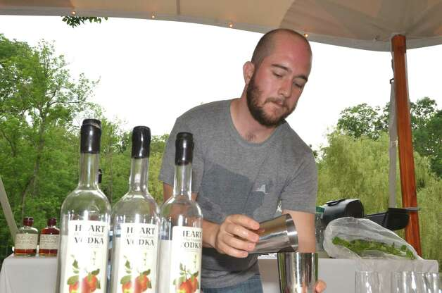 Tuthilltown Spirits (Gardiner, NY) owner Gable Erenzo mixes a refreshing drink of Heart of the Hudson vodka, mint infused lemonade, and fresh strawberries for thirsty guests, during the Dine with Design picnic at the Glass House.  Saturday, June 9, 2012, New Canaan, Conn. Photo: Jeanna Petersen Shepard