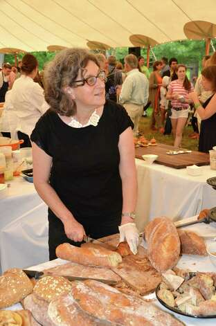 Margaret Sapir from Wave Hill Breads in Norwalk cuts up some of her fresh bread and chats with guests at the Dine with Design event last Saturday, June 9, 2012, in New Canaan, Conn. Photo: Jeanna Petersen Shepard