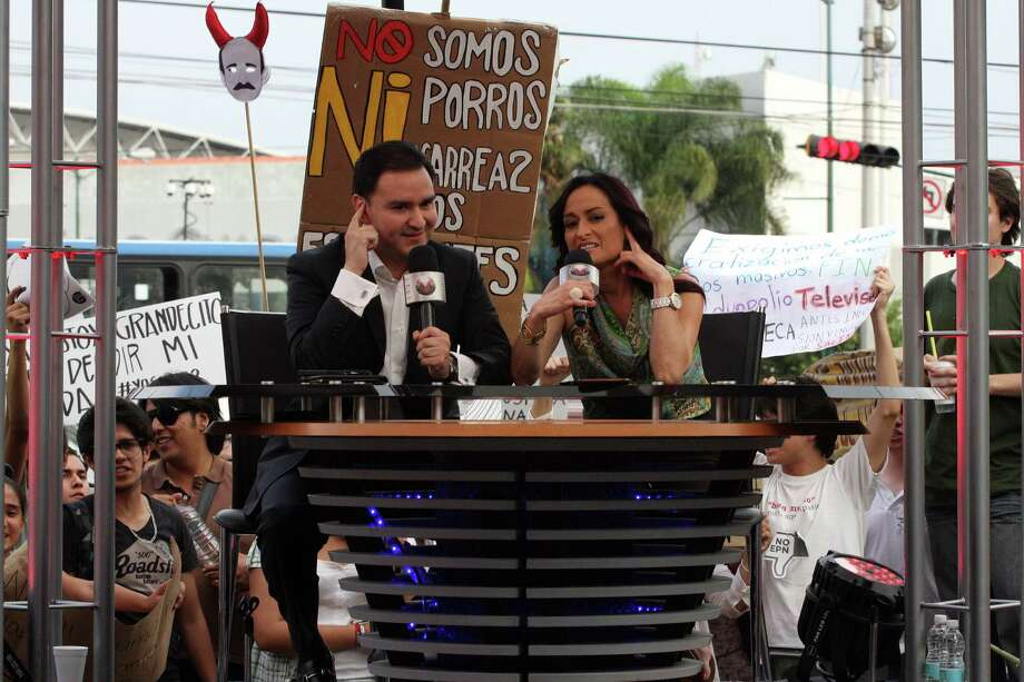 "Members of the ""Yo soy 132"" (I Am #132) movement (background) shout slogans behind TV presenters Carlos Zuniga (L) and Marisa Iglesias, in Guadalajara city, Mexico on June 10, 2012. Mexico will hold presidential elections next July 1, 2012. AFP PHOTO/Hector Guerrero        (Photo credit should read HECTOR GUERRERO/AFP/GettyImages) Photo: HECTOR GUERRERO, Getty Images / 2012 AFP"