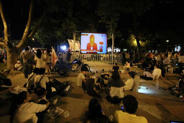 People watch the debate of presidential candidates on a giant screens at the street of Guadalajara, Mexico on June 10, 2012.  Four presidential candidates are taking part of the second debate promoted by the Federal Electoral Institute.     AFP PHOTO / Hector Guerrero        (Photo credit should read HECTOR GUERRERO/AFP/GettyImages) Photo: AFP, Getty Images / 2012 AFP