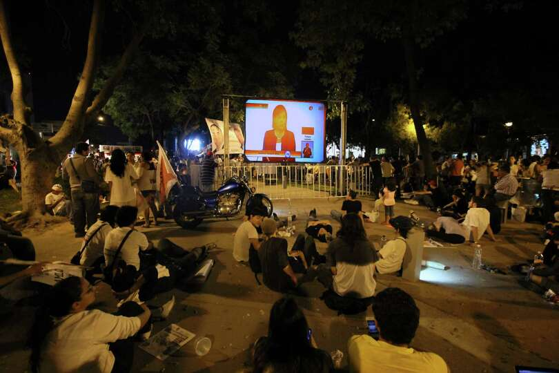 People watch the debate of presidential candidates on a giant screens at the street of Guadalajara,