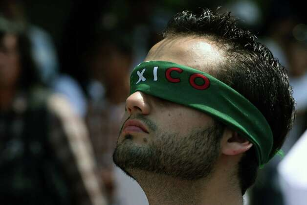 "A member of the ""Yo soy 132"" (I Am #132) movement covers his eyes during a protest against the Mexican television, to demand fair broadcasting and electoral information in Guadalajara city, Mexico on June 10, 2012. Mexico will hold presidential elections next July 1, 2012. AFP PHOTO/Hector Guerrero        (Photo credit should read HECTOR GUERRERO/AFP/GettyImages) Photo: HECTOR GUERRERO, Getty Images / 2012 AFP"