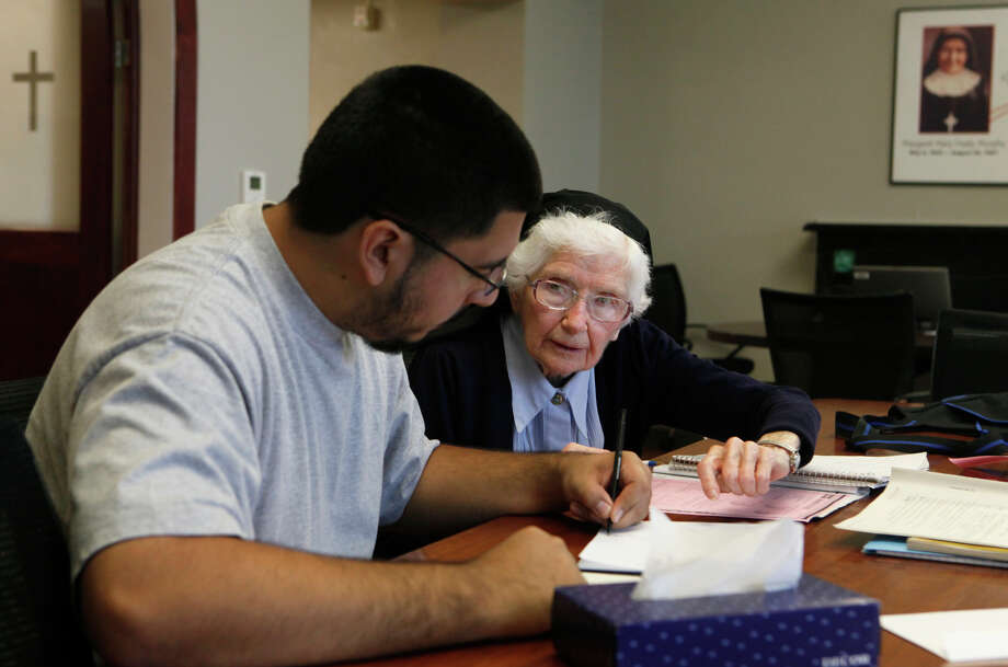 Sister Ferdinand, 90, still tutors students at  Healy-Murphy Center downtown. Here, she works with senior Joaquin Arias, 18. Photo: John Davenport, San Antonio Express-News