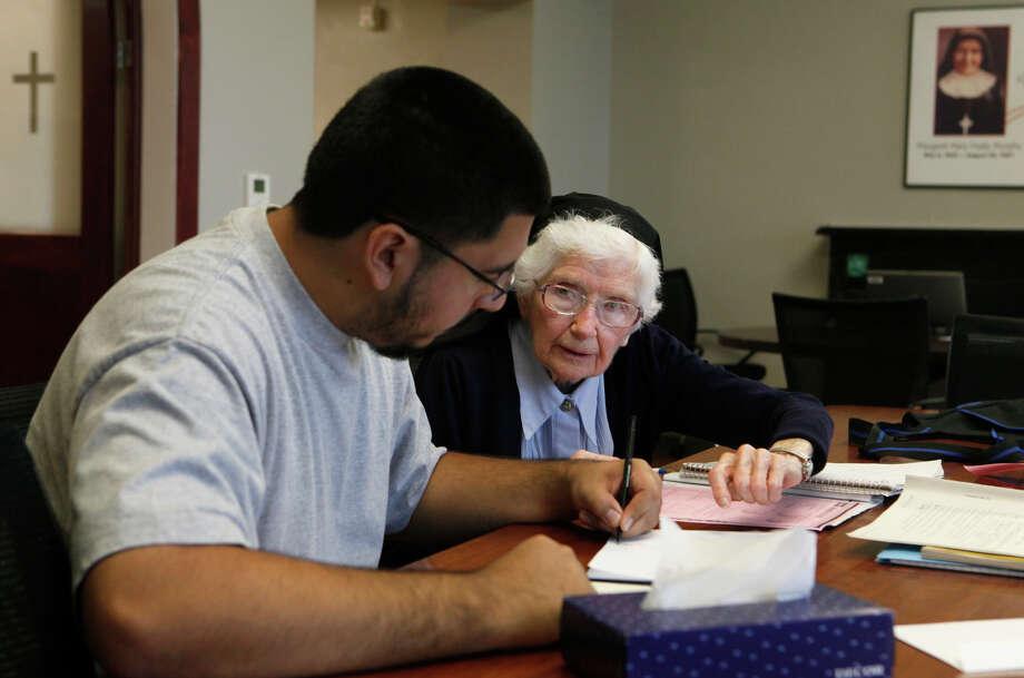 Sister Ferdinand, 90, still tutors students at Healy-Murphy Center downtown. Here, she works with senior Joaquin Arias, 18. Photo: John Davenport, San Antonio Express-News