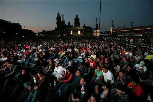 People gather to watch a broadcast of the second presidential debate on screens at Mexico City's Zocalo plaza, Sunday, June 10, 2012. Mexico will hold presidential elections on July 1. (AP Photo/Marco Ugarte) Photo: Marco Ugarte, Associated Press / AP