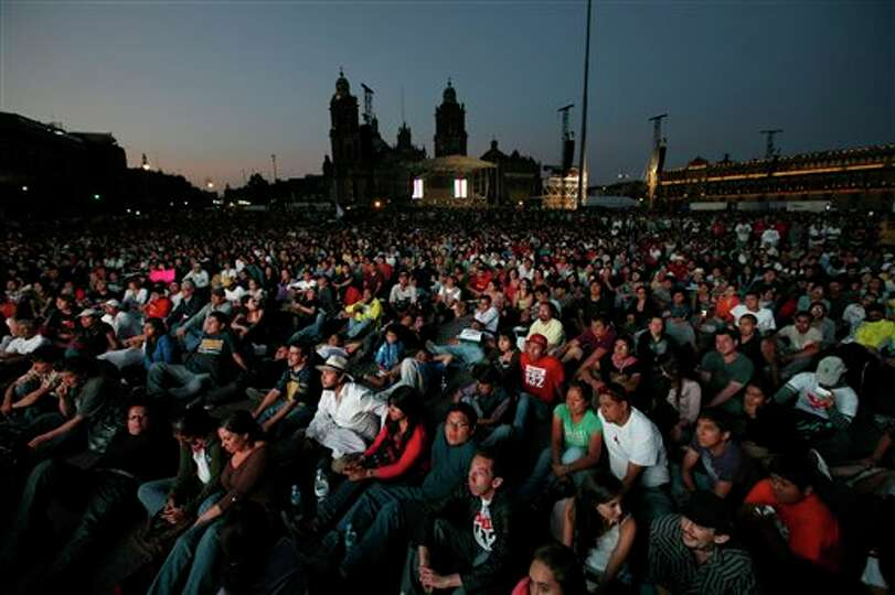 People gather to watch a broadcast of the second presidential debate on screens at Mexico City's Zoc