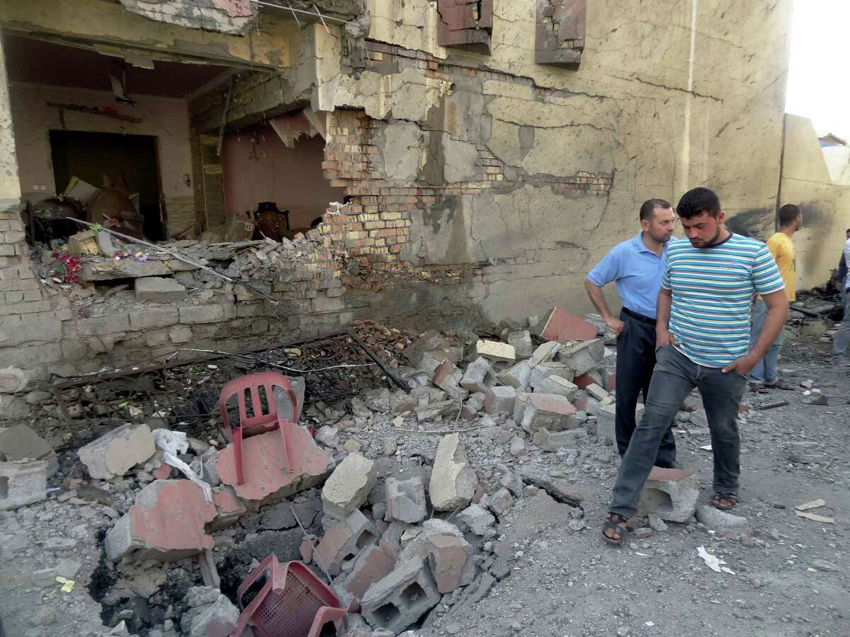 Iraqis inspect the site of a car bomb in the northern Iraqi city of Kirkuk on Wednesday as a wave of bombings and shootings hit Iraq during a major Shiite religious commemoration, killing scores of people and wounding dozens more, security and medical officials said. (MARWAN IBRAHIM/AFP/GettyImages)