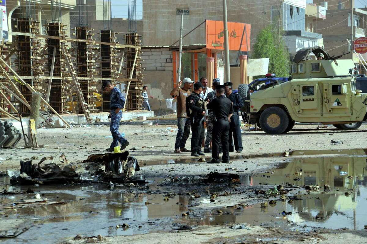 Security forces inspect the scene where two car bombs exploded minutes apart in Hillah, about 60 miles  south of Baghdad on Wednesday. Coordinated car bombs struck mainly Shiite pilgrims in several Iraqi cities, killing and wounding dozens of people, police said, in one of the deadliest attacks since U.S. troops withdrew from the country. (AP Photo)