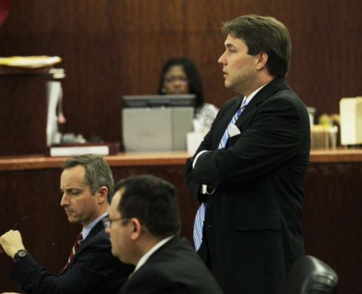 Defense attorney Neal Davis, right, stands behind his client, Raul Rodriguez, seated center, on W
