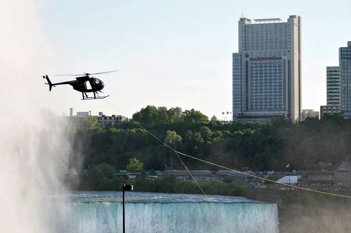 A helicopter tows a guide wire over Niagara Falls across the gorge, Tuesday, June 12, 2012 in preparation for Nik Wallenda's high wire walk across the falls on Friday evening, in Niagara Falls, N.Y. Daredevil Nik Wallenda estimates his history-making, U.S.-to-Canada walk by way of a cable strung over the brink will cost about $1.2 million to $1.3 million. That includes fabrication and installation of the custom-made steel wire, permits and security on both sides of the border, travel, and marketing. (AP Photo/The Niagara Gazette, Dan Cappellazzo) BUFFALO NEWS OUT; BATAVIA DAILY NEWS OUT