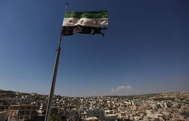 A Syrian revolutionary flag waves on top of a building on the outskirts of Aleppo, Syria, Tuesday, June 12, 2012.  On Tuesday, Syrian forces pelted the eastern city of Deir el-Zour with mortars as anti-government protesters were dispersing before dawn Tuesday, killing several people, activists said. The offensives were part of an escalation of violence in recent weeks that has brought more international pressure on President Bashar Assad's regime faces over its brutal tactics against the opposition. The U.N. accused the government of using children as human shields in a new report. (AP Photo) Photo: Anonymous, Associated Press