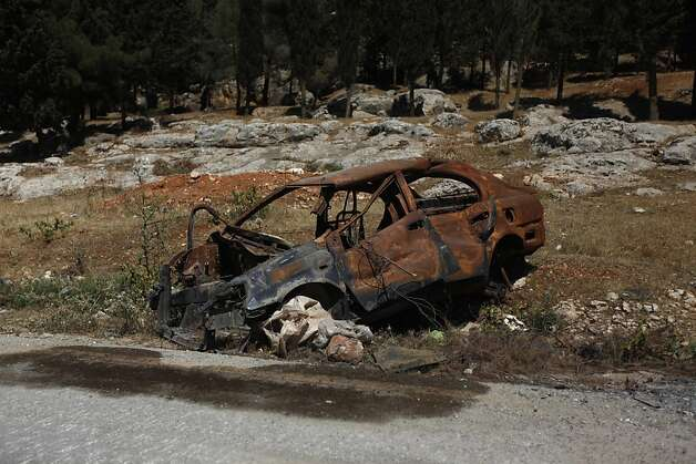 A destroyed car is seen on the side of a street on the outskirts of Aleppo, Syria, Tuesday, June 12, 2012.   On Tuesday, Syrian forces pelted the eastern city of Deir el-Zour with mortars as anti-government protesters were dispersing before dawn Tuesday, killing several people, activists said. The offensives were part of an escalation of violence in recent weeks that has brought more international pressure on President Bashar Assad's regime faces over its brutal tactics against the opposition. The U.N. accused the government of using children as human shields in a new report. (AP Photo) Photo: Anonymous, Associated Press