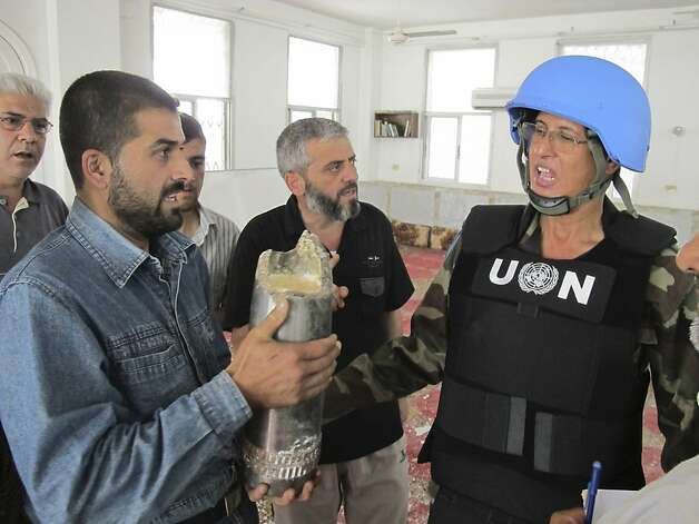 A resident, left, shows a shell to a United Nations observer, right,  after shelling at the Talbisah area in Homs city Syria Monday June 11, 2012. (AP Photo/David Manyua/United Nations ) Photo: David Manyua, Associated Press