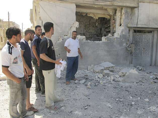 Residents stand next to a shop that was damaged after shelling at the Talbisah area in Homs city Syria Monday June 11, 2012. (AP Photo/David Manyua/United Nations ) Photo: David Manyua, Associated Press