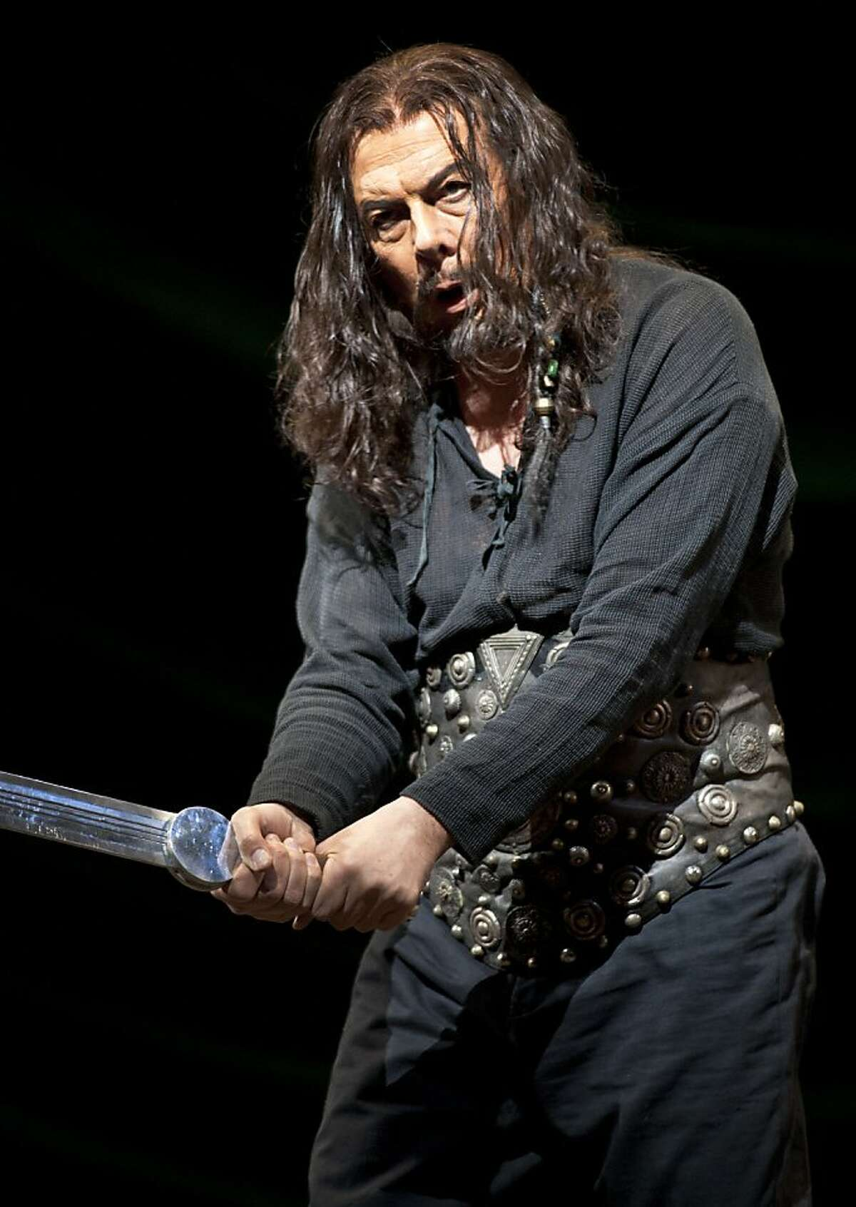 Attila, King of the Huns, played by Ferruccio Furlanetto holds up a sword as he sings at the front of the stage during the production of Attila. San Francisco's Opera season continues with