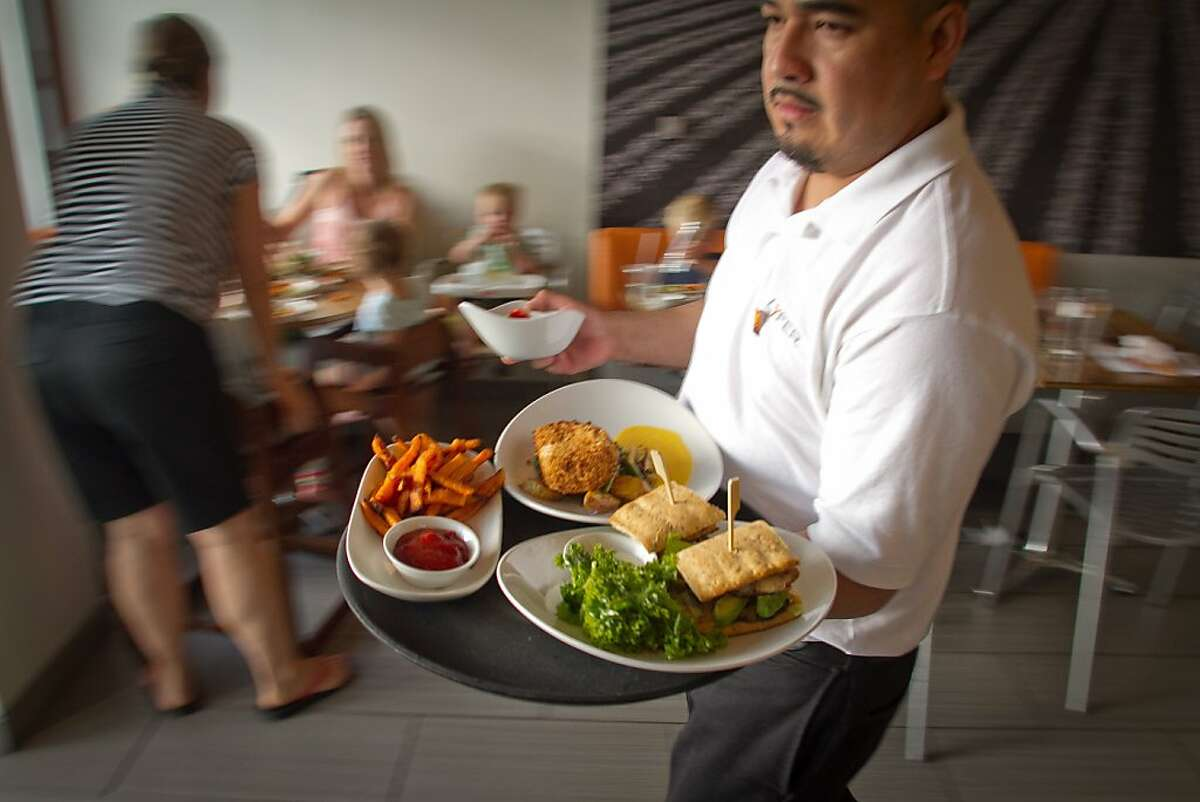 A server brings out food during dinner swerve at Lyfe restaurant in Palo Alto, Calif., on Saturday, June 9th, 2012.