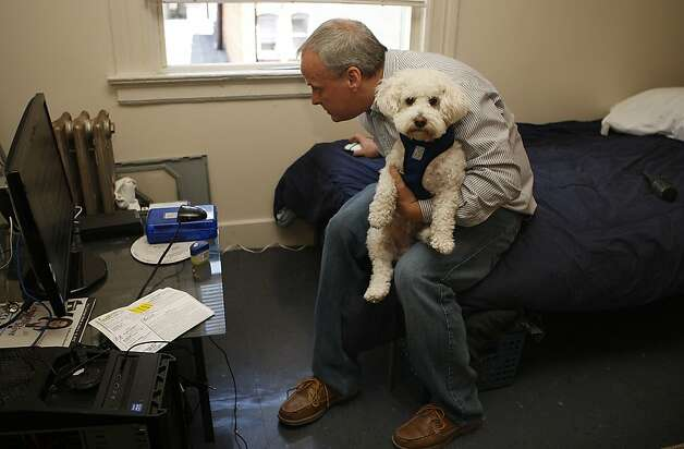 Matt Traywick with his dog Charlie as he checks the internet in his Tenderloin home in San Francisco, California, on Tuesday, June 12, 2012. Photo: Liz Hafalia, The Chronicle
